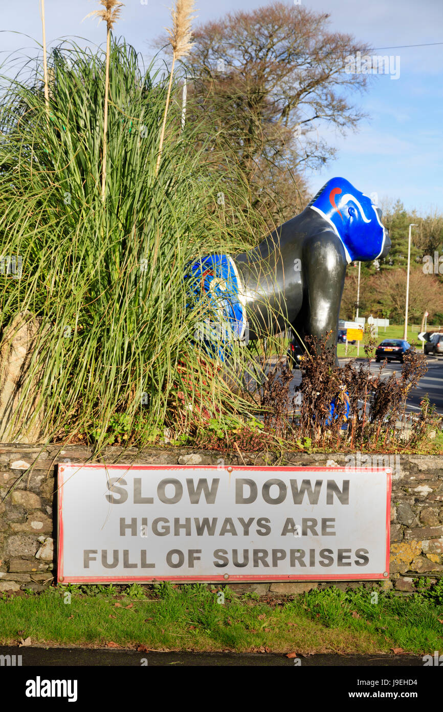 Nacho, a painted statue from Paignton Zoo's Great Gorilla Project stands above a road safety notice at Woolwell - Stock Image