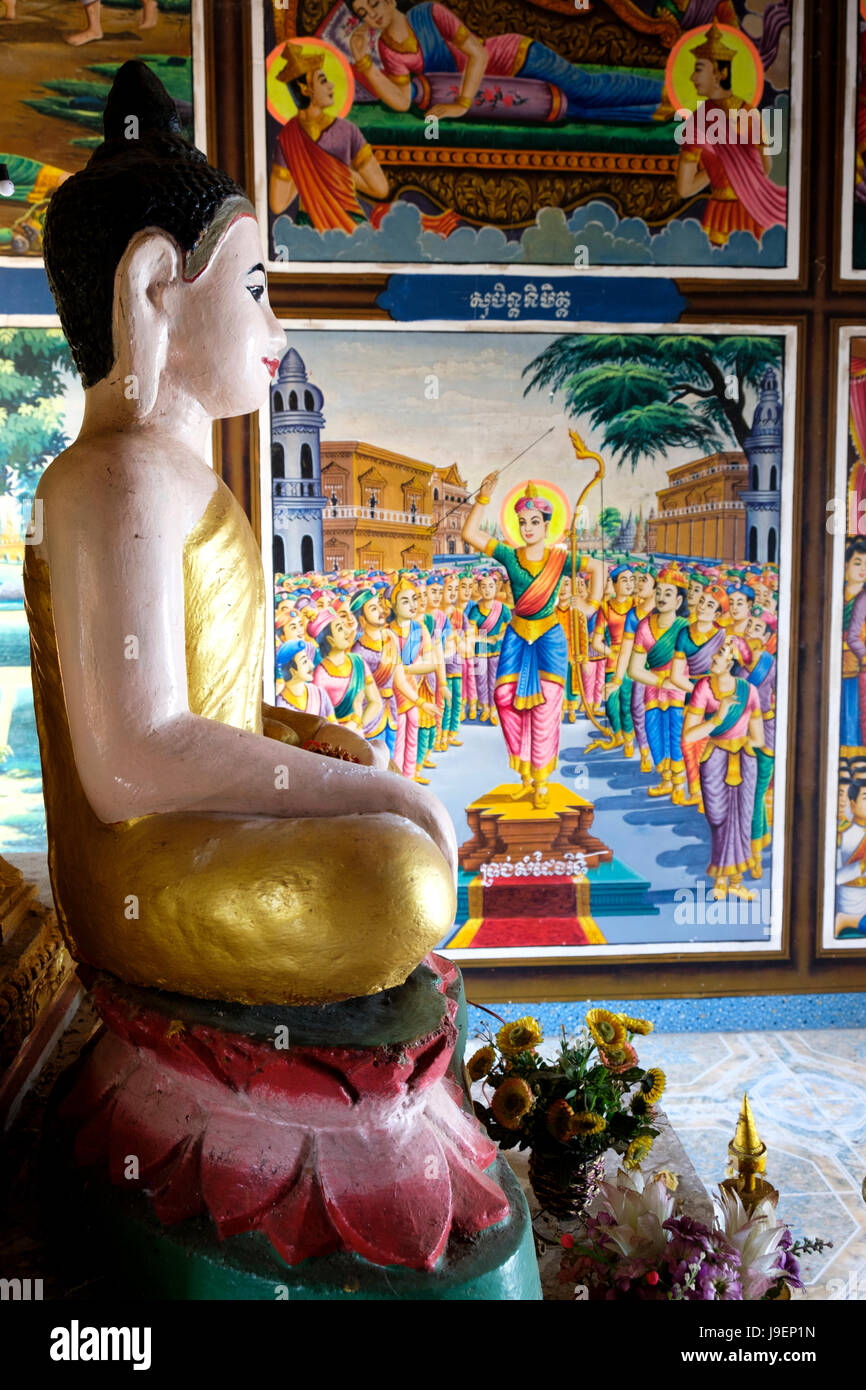 Buddha effigy in front of a painted mural depicting scenes from the life of the Buddha in Phnom Sambok temple near - Stock Image