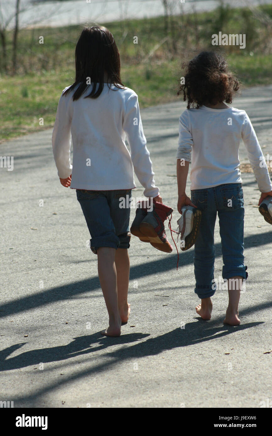 Two little girls walking barefooted on alley - Stock Image