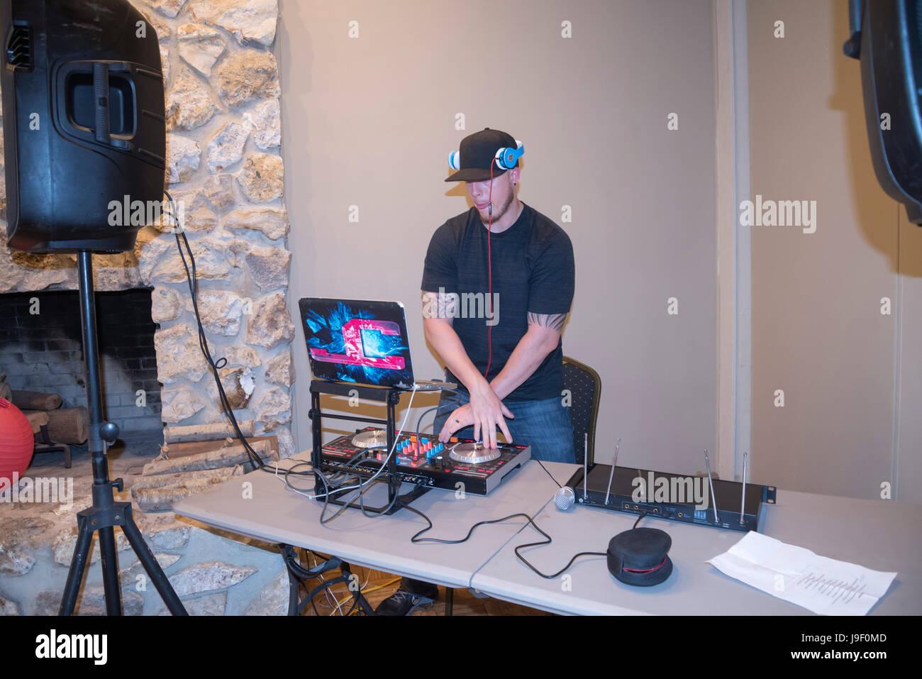 Event Disc Jockey mixes the sounds. - Stock Image