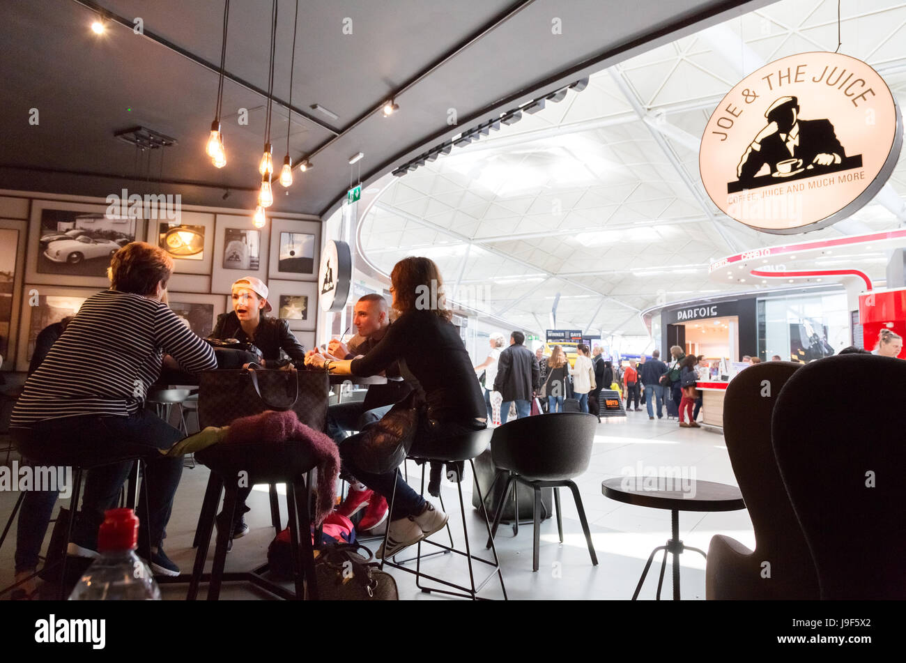 People drinking at the Joe & the Juice cafe, Stansted airport departures lounge, London UK - Stock Image