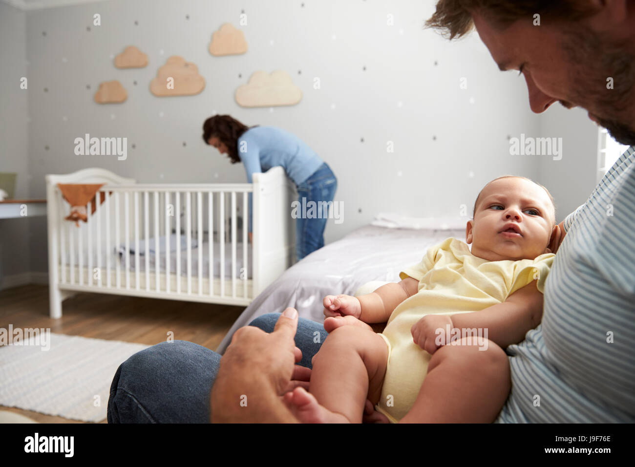 Mother Making Up Bed In Nursery Cot For Newborn Son - Stock Image