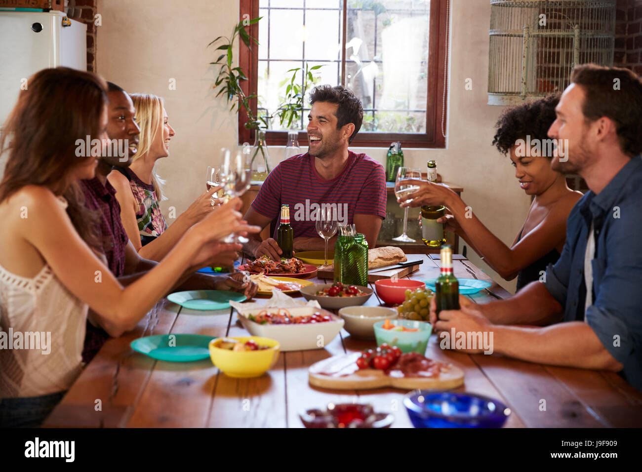 Six young adult friends sitting at table for a dinner party - Stock Image