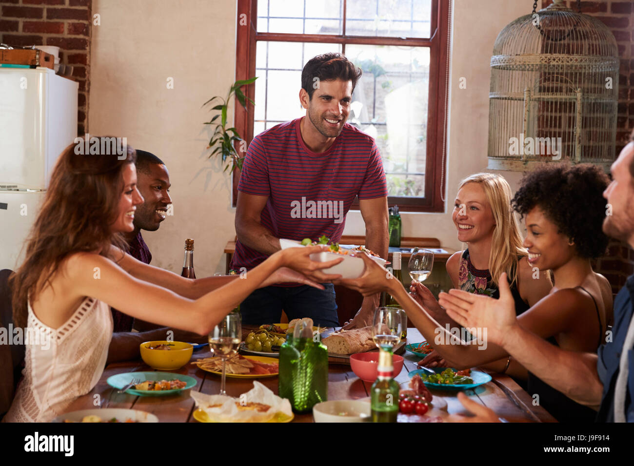 Host and friends pass food round the table at a dinner party - Stock Image