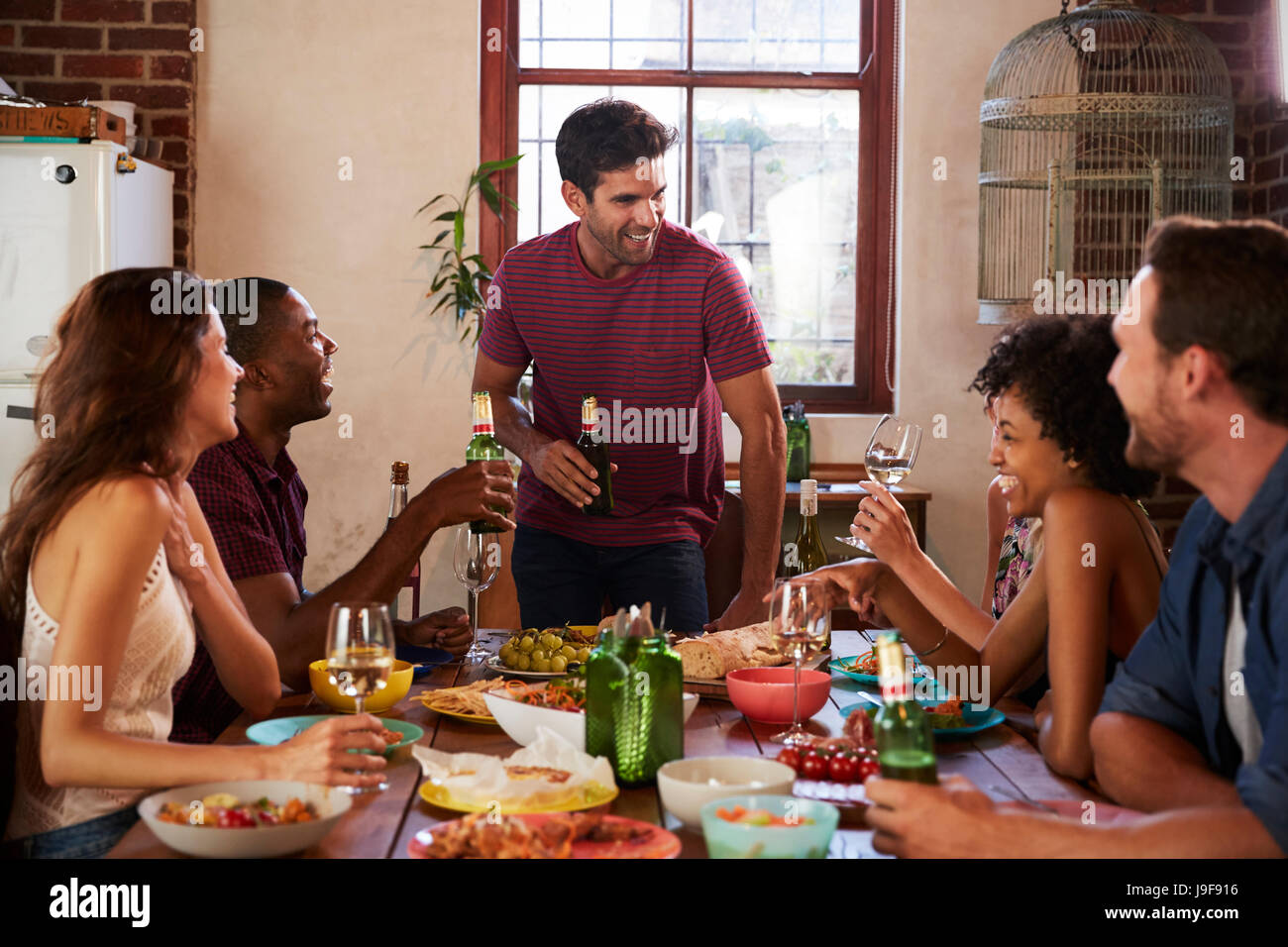 Friends with drinks at the table during a dinner party - Stock Image