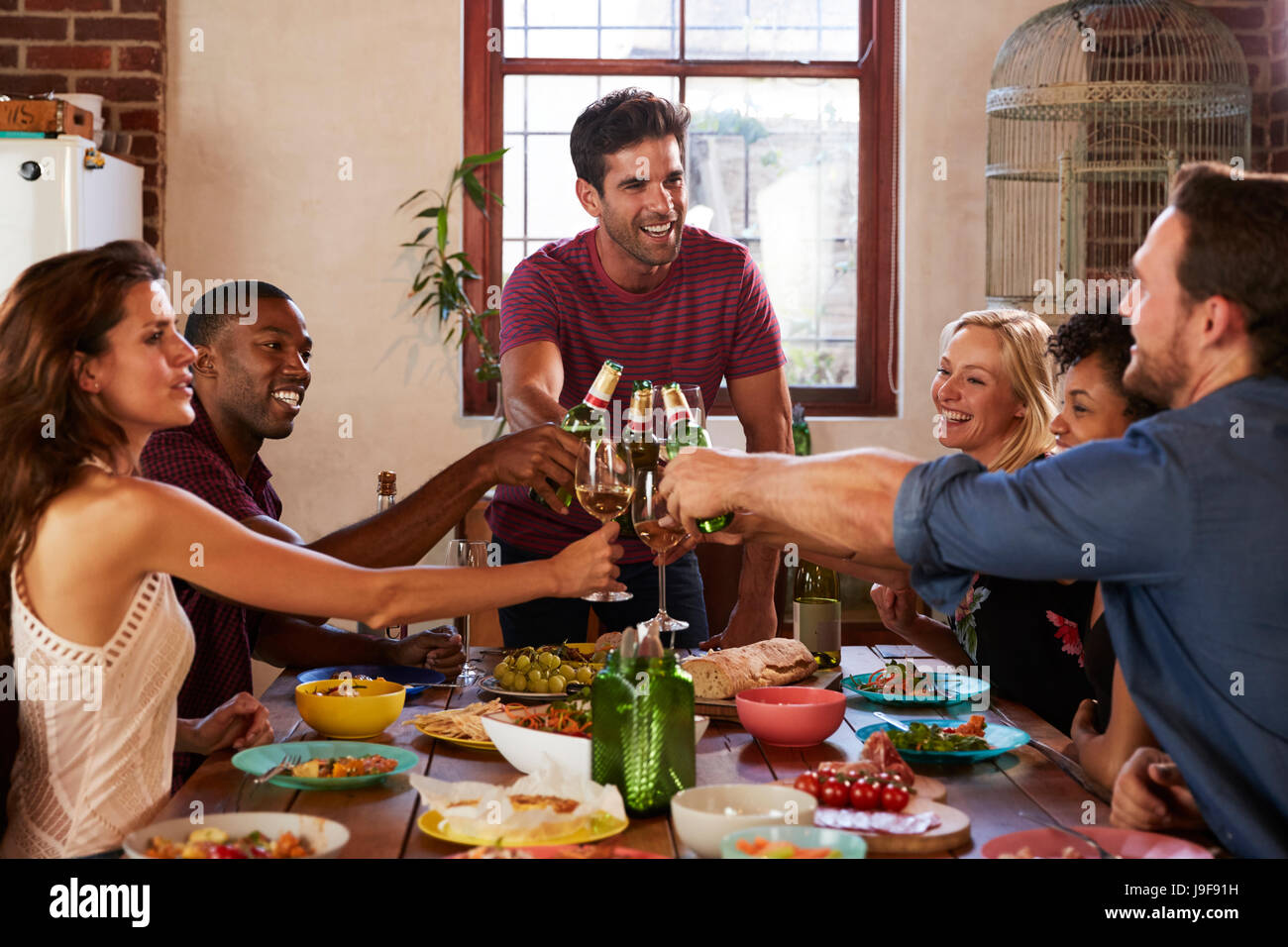 Host and friends making a toast at a dinner party - Stock Image