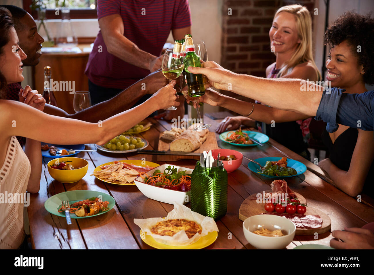 Host and friends making a toast at a dinner party, close up - Stock Image