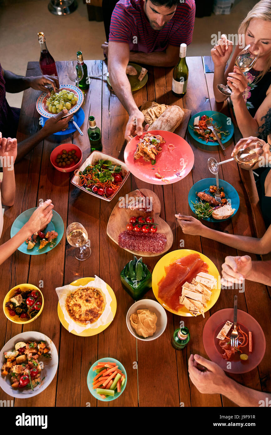 Overhead shot of friends passing food across a dinner table - Stock Image