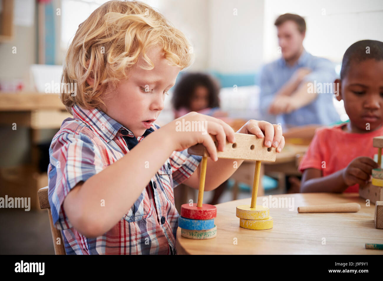 Montessori Pupil Working At Desk With Wooden Shapes - Stock Image
