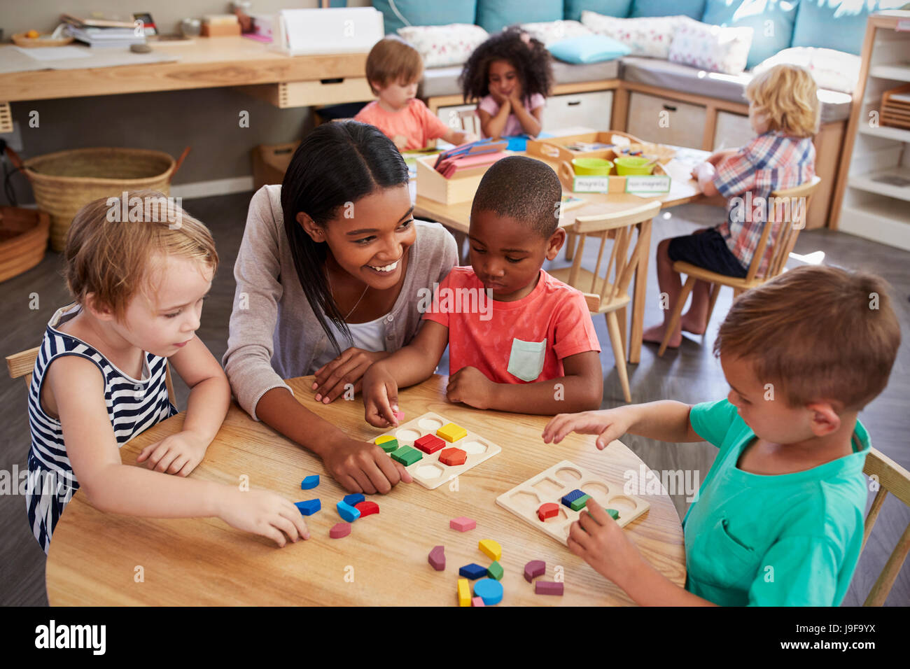 Teacher And Pupils Using Wooden Shapes In Montessori School - Stock Image