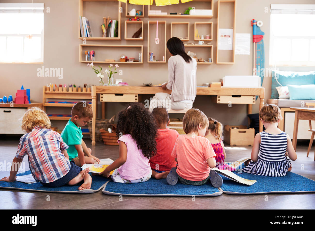 Pupils At Montessori School Reading Independently In Classroom - Stock Image