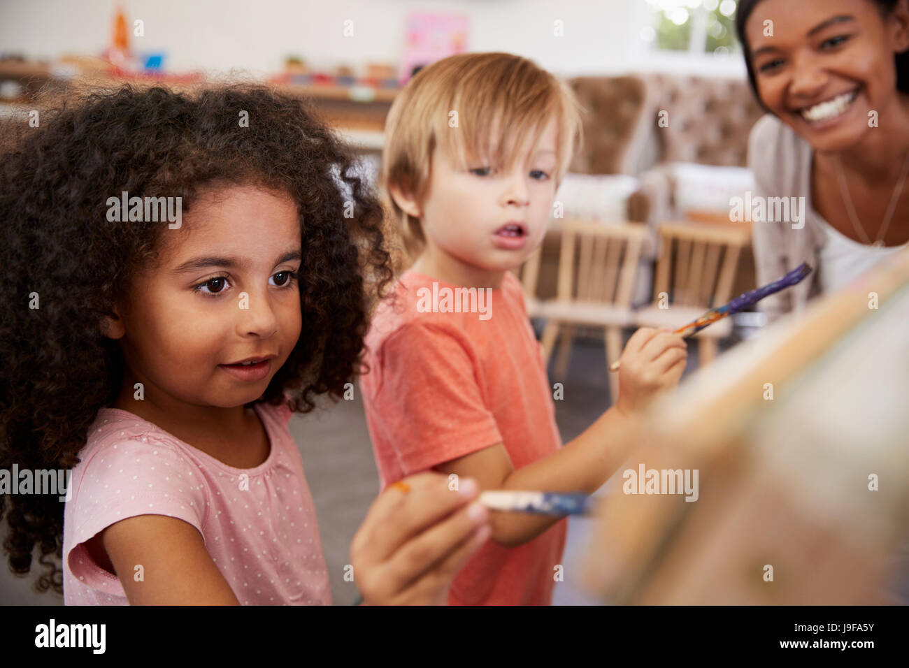 Teacher At Montessori School Helping Children in Art Class - Stock Image
