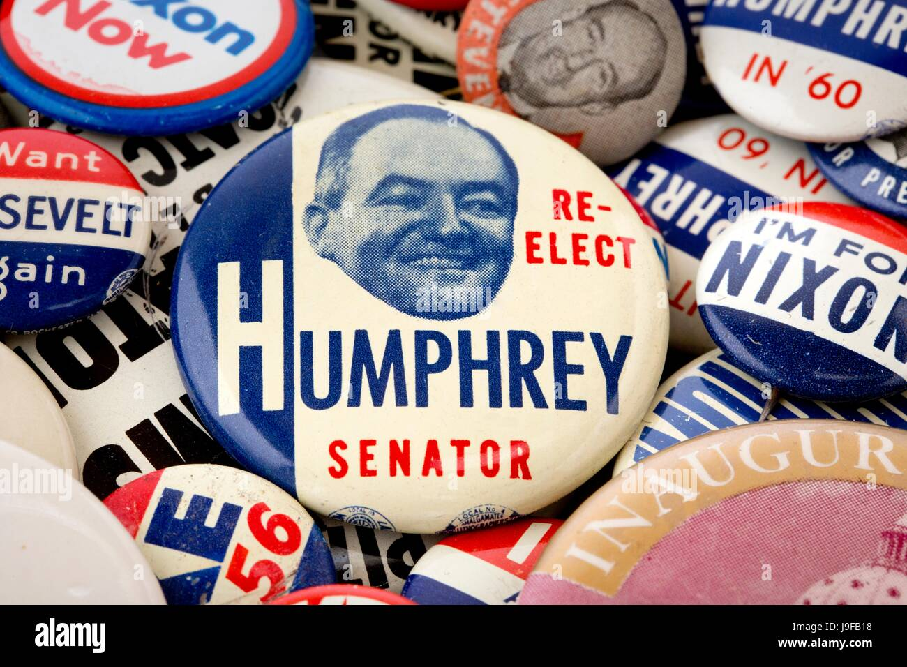 A 1954 Re-Elect Hubert H. Humphrey Senator Pinback Button on top of a pile of political pin-back buttons - Stock Image
