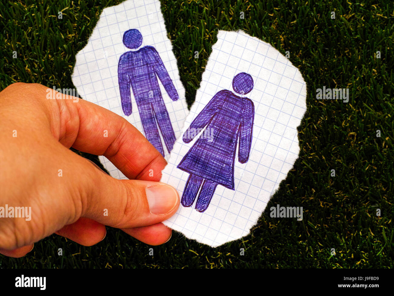 Person hand holding piece of paper with hand drawn woman figure. Other piece of paper with drawn man figure on grass - Stock Image