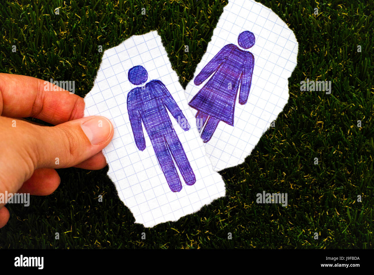 Person fingers holding piece of paper with hand drawn man figure. Other piece of paper with drawn woman figure on - Stock Image