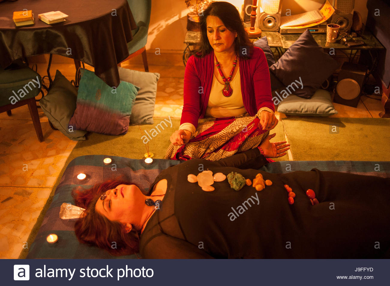 A patient receives Chakra treatment using crystals. - Stock Image