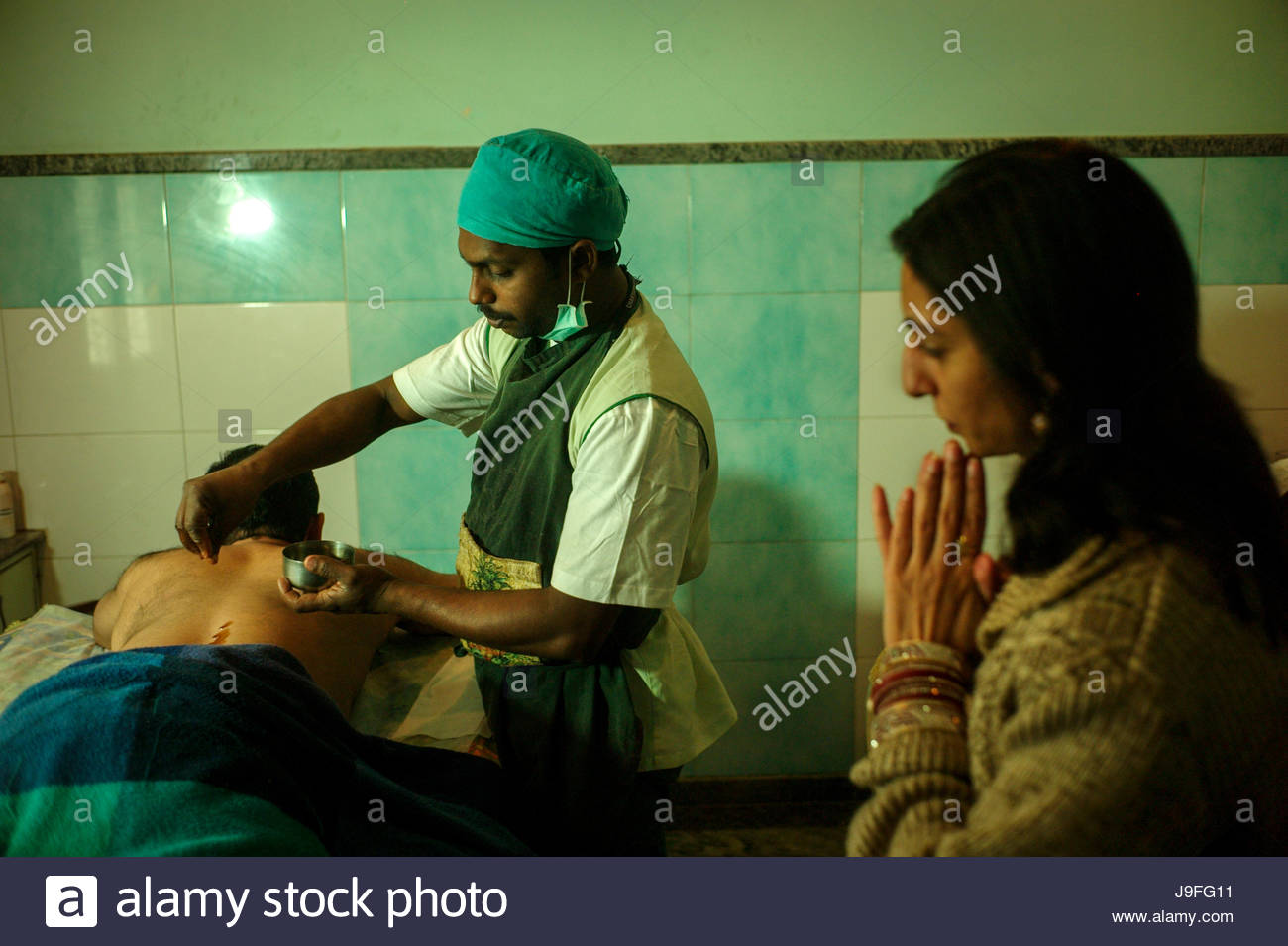 An Ayurvedic practitioner treats a patient for back pain using Patra Pinda Sweda Therapy at an Ayurvedic center, - Stock Image