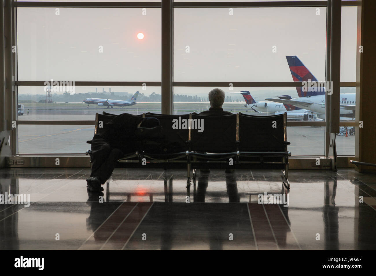 Just after sunrise, a traveler sits in Ronald Reagan National Airport and watches airplanes on the runway. - Stock Image