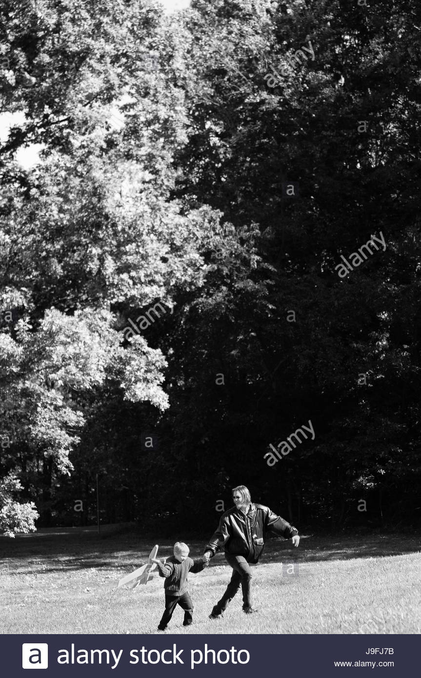 A five-year old boy and his father play with a toy airplane. - Stock Image
