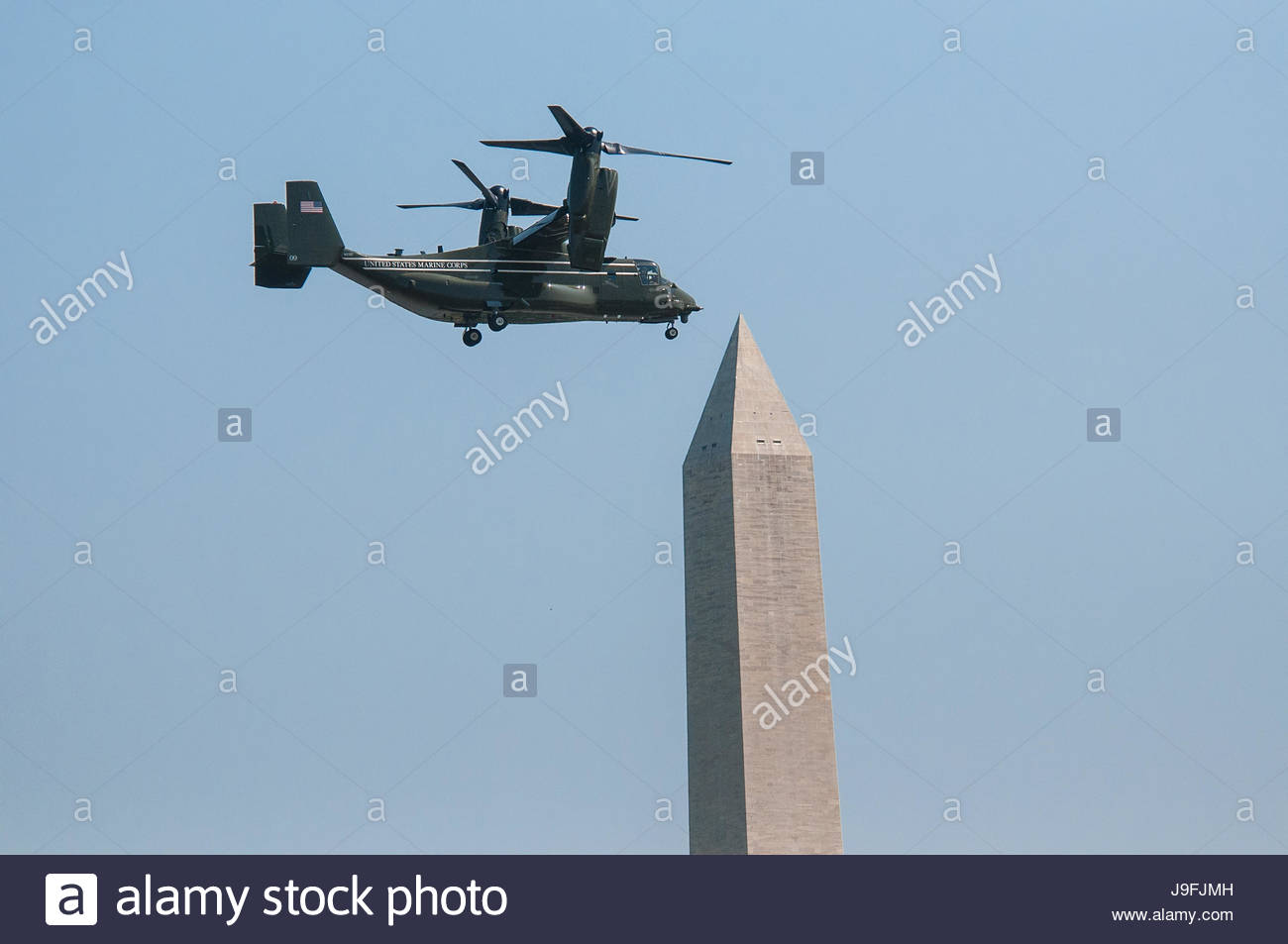 A military helicopter flies past the Washington Monument. - Stock Image