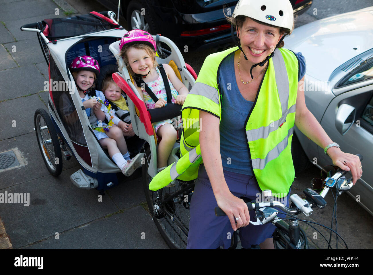 Woman cyclist on bike / bicycle with + 3 children; Co Pilot child seat with helmet & towing cycle Chariot trailer - Stock Image