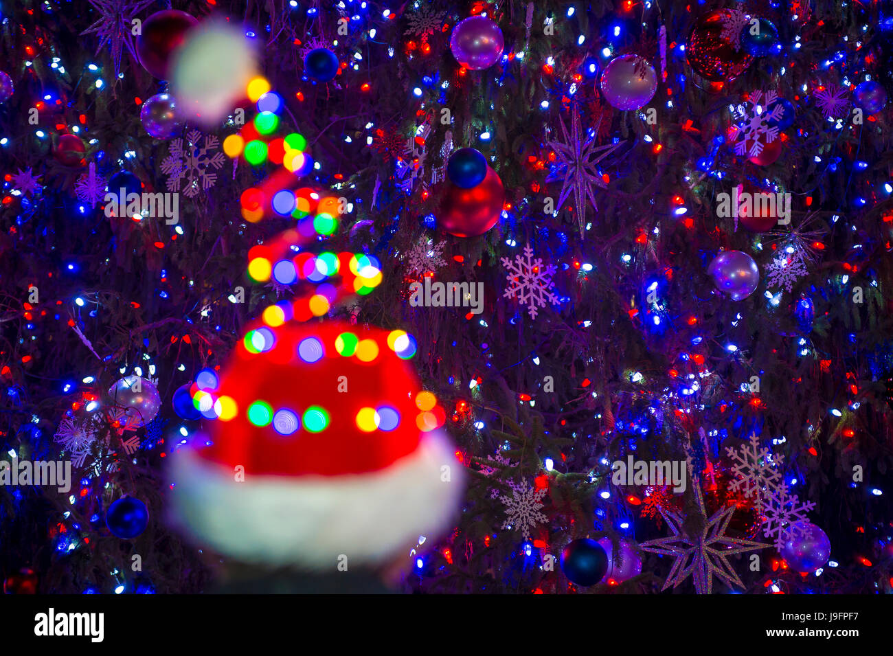 Colorful holiday lights glow on a Santa hat in front of a twinkling Christmas tree background - Stock Image