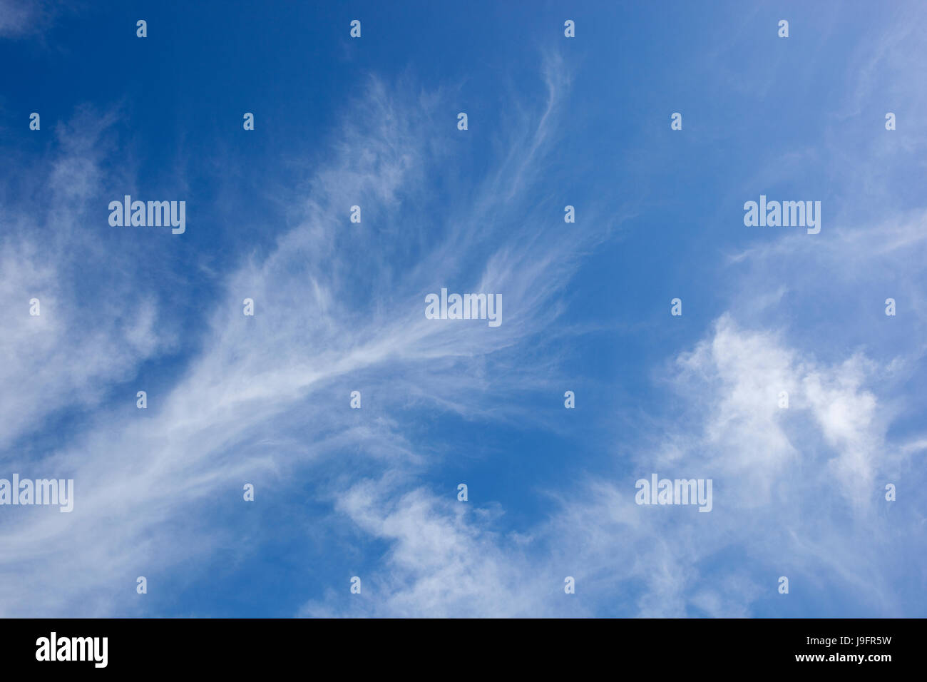 a blue sky background with white wispy cloud - Stock Image