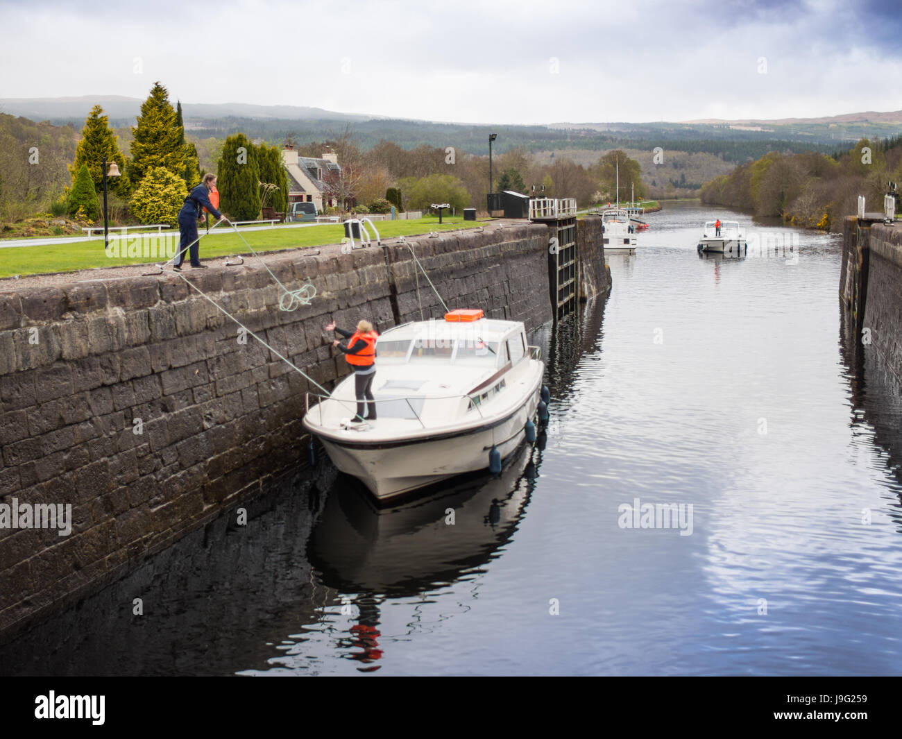 Charter boats going though Cullochy lock, lock keeper handling ropes - Stock Image