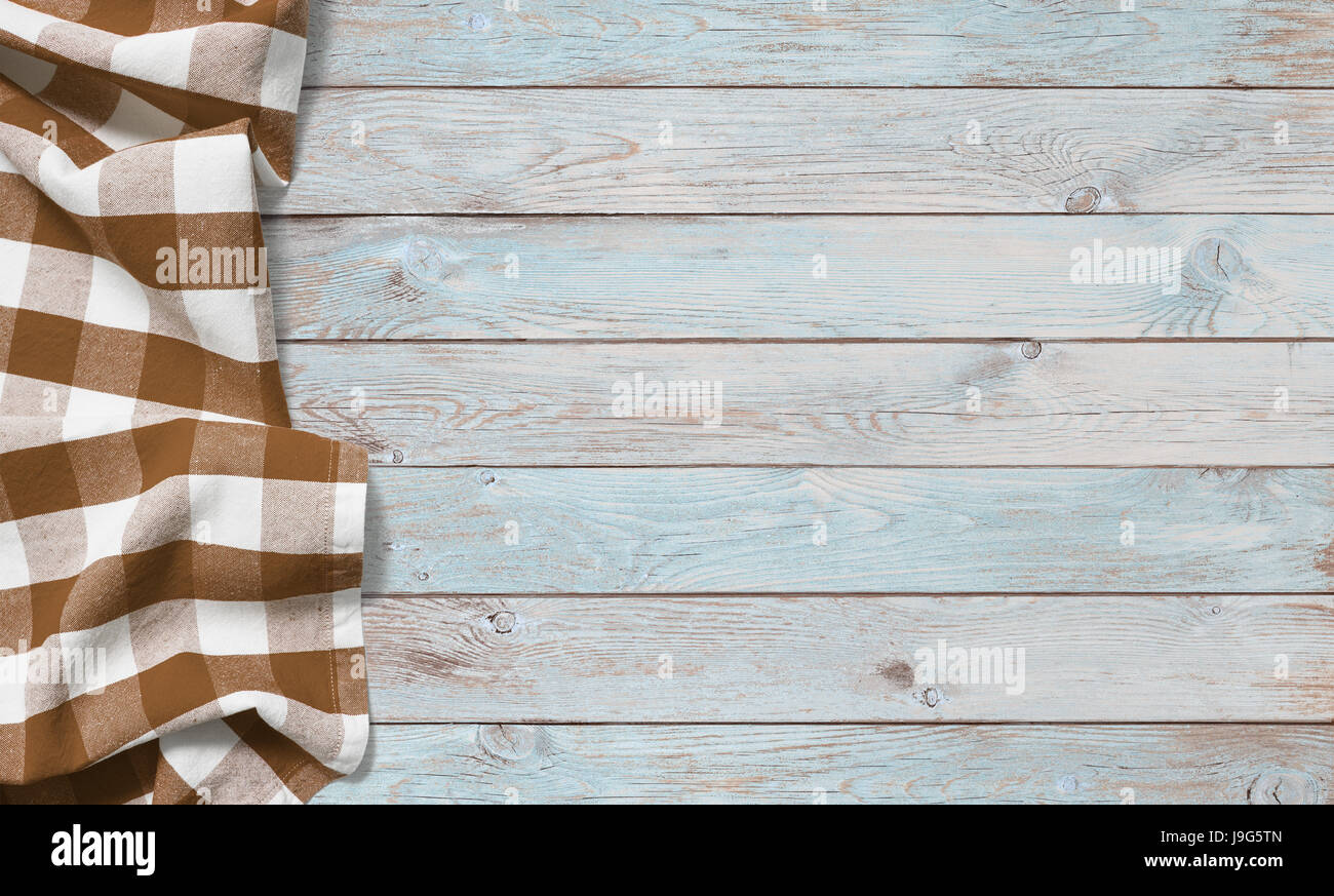 brown picnic cloth on blue wood table - Stock Image
