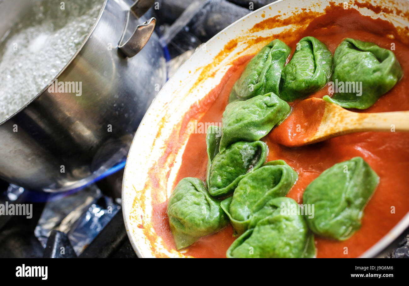 Green Tortelloni. Typical Bolognese homemade fresh stuffed pasta at the end of cooking just a moment before serving. - Stock Image