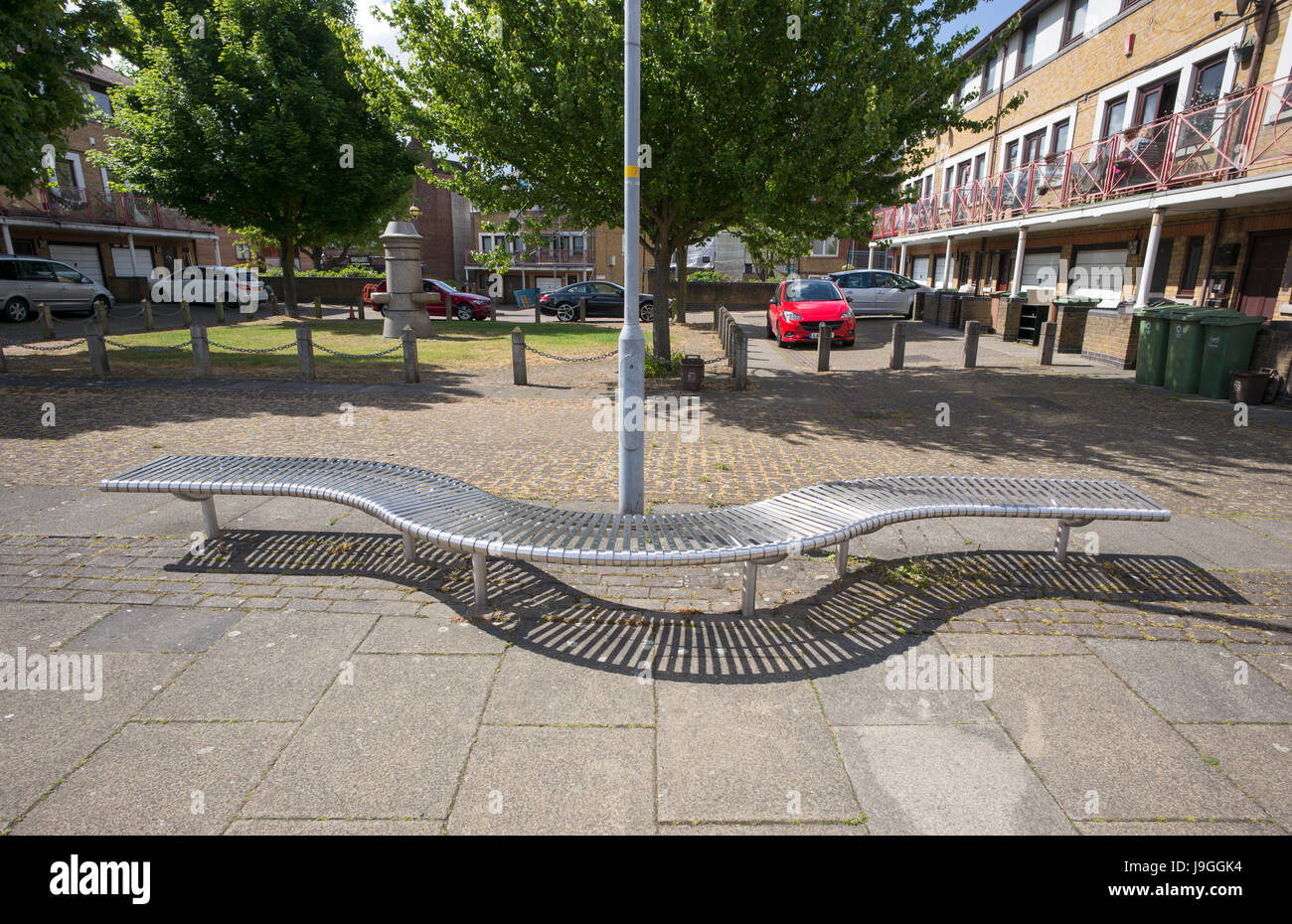 Curved stainless steel bench at base of lamp post near housing, Rotherhithe, London, UK Stock Photo