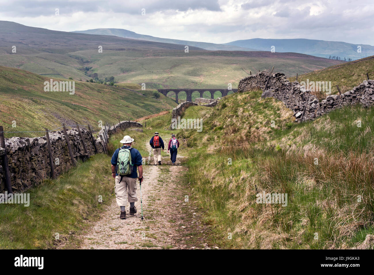 Walkers on an old drovers road, now the Pennine Bridleway, at Arten Gill. Dentdale, Yorkshire Dales National Park, - Stock Image