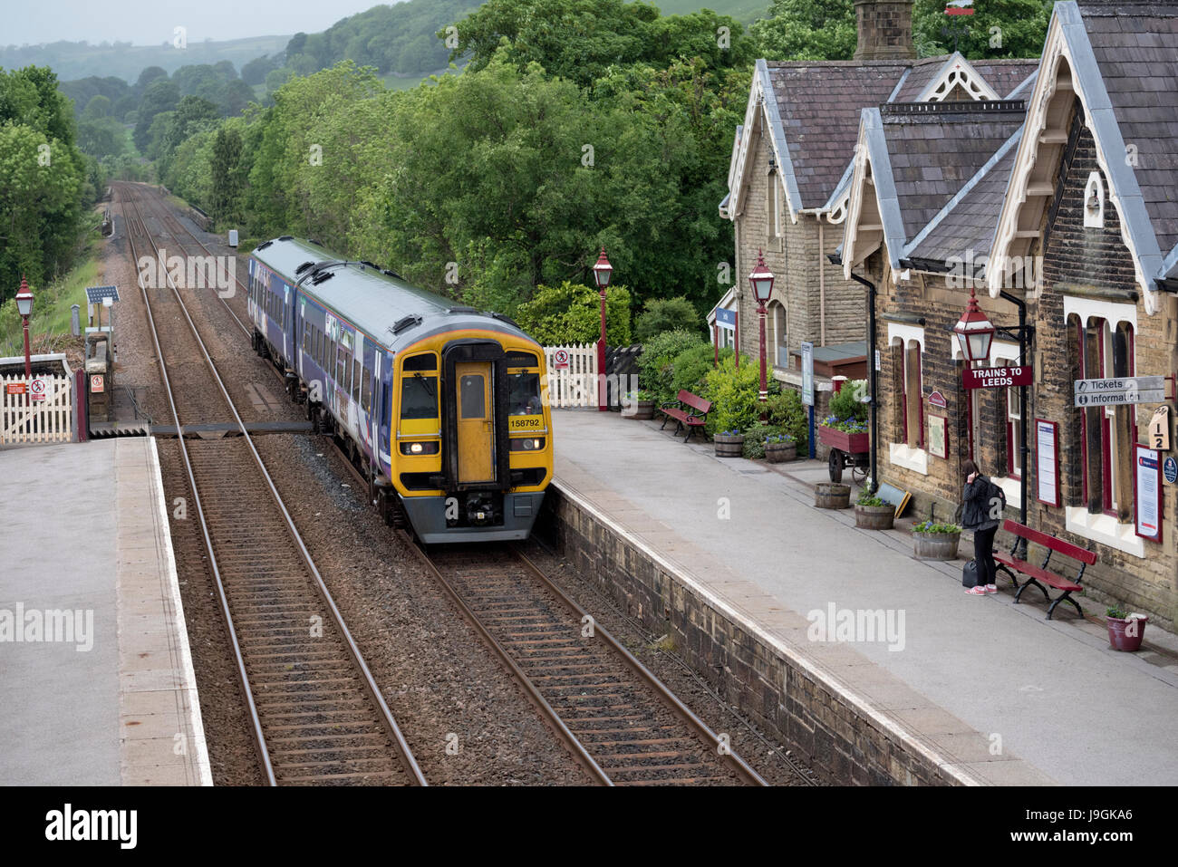 A Sprinter train from Carlisle arriving at Settle station, North Yorkshire, en route to Leeds, UK. - Stock Image