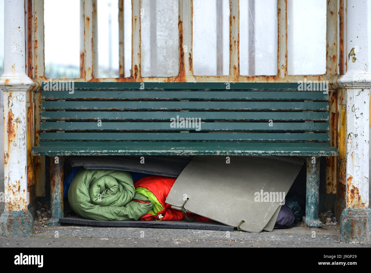 Homelessness. Homeless person's bedding stored under a bench in a bus stop. - Stock Image