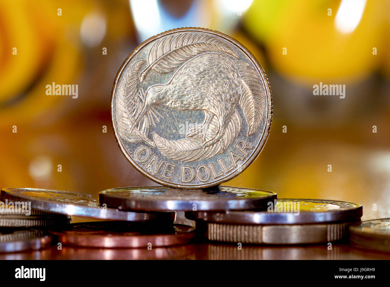 New Zealand dollar on a bed of coins. - Stock Image