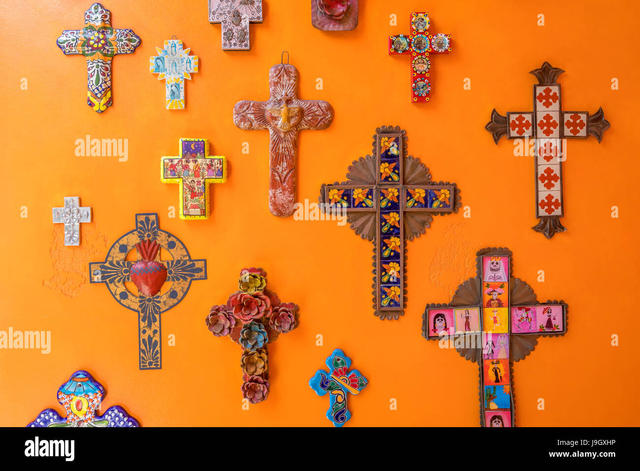 Various crosses decorating an orange wall - Stock Image
