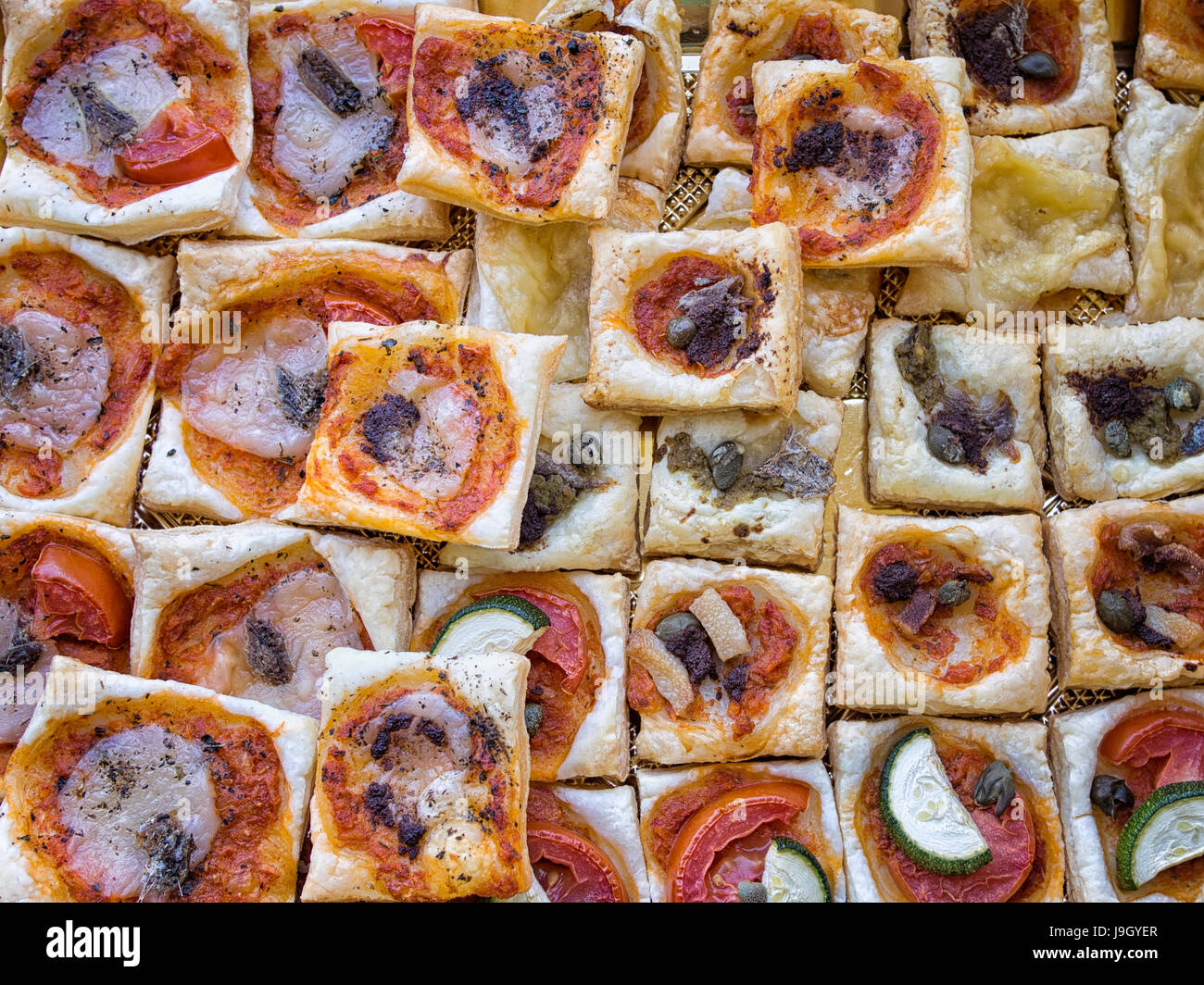 Italian aperitif. Flaky pastry bites with pizza style toppings. - Stock Image