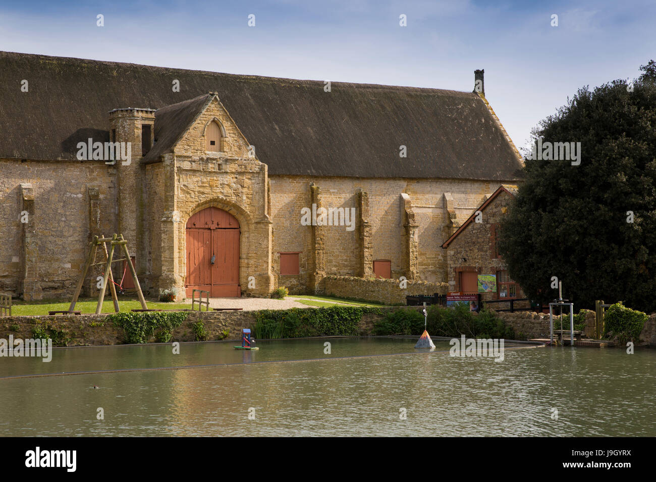 UK England, Dorset, Abbotsbury, Church Street, Medieval former Benedictine Abbey Tithe Barn across fish pond - Stock Image
