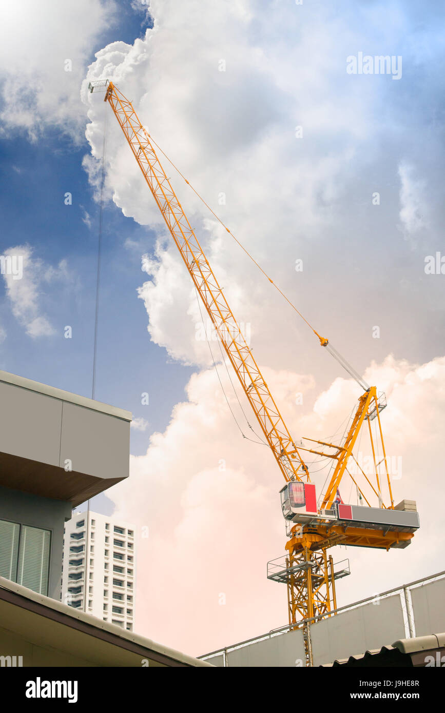 Work in progress - Tower crane above the roof against the sky at sunset - Stock Image