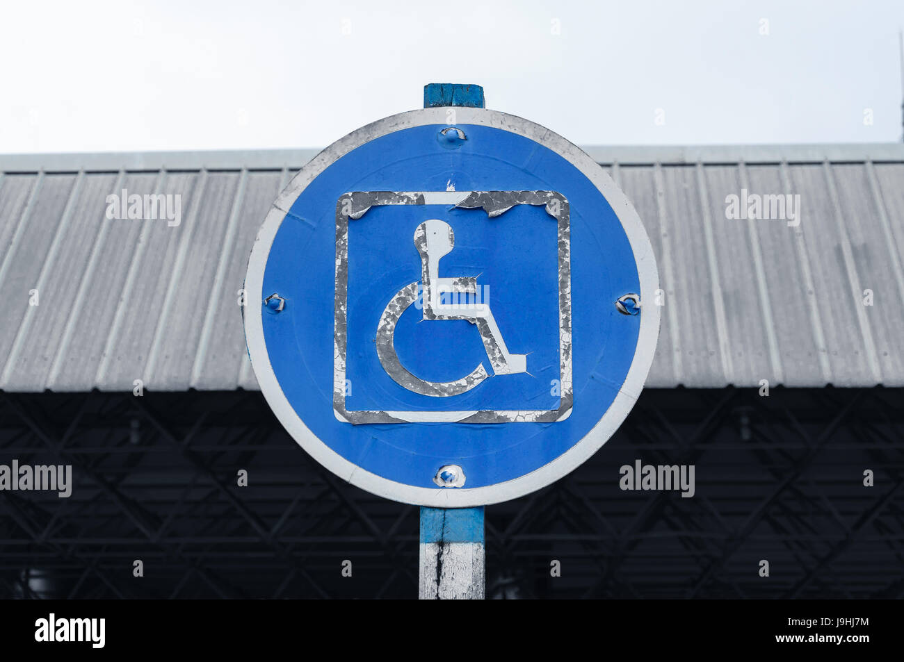 Blue and white warning sign reserved only for people with disabilities. Wheelchair plate peeling paint. - Stock Image