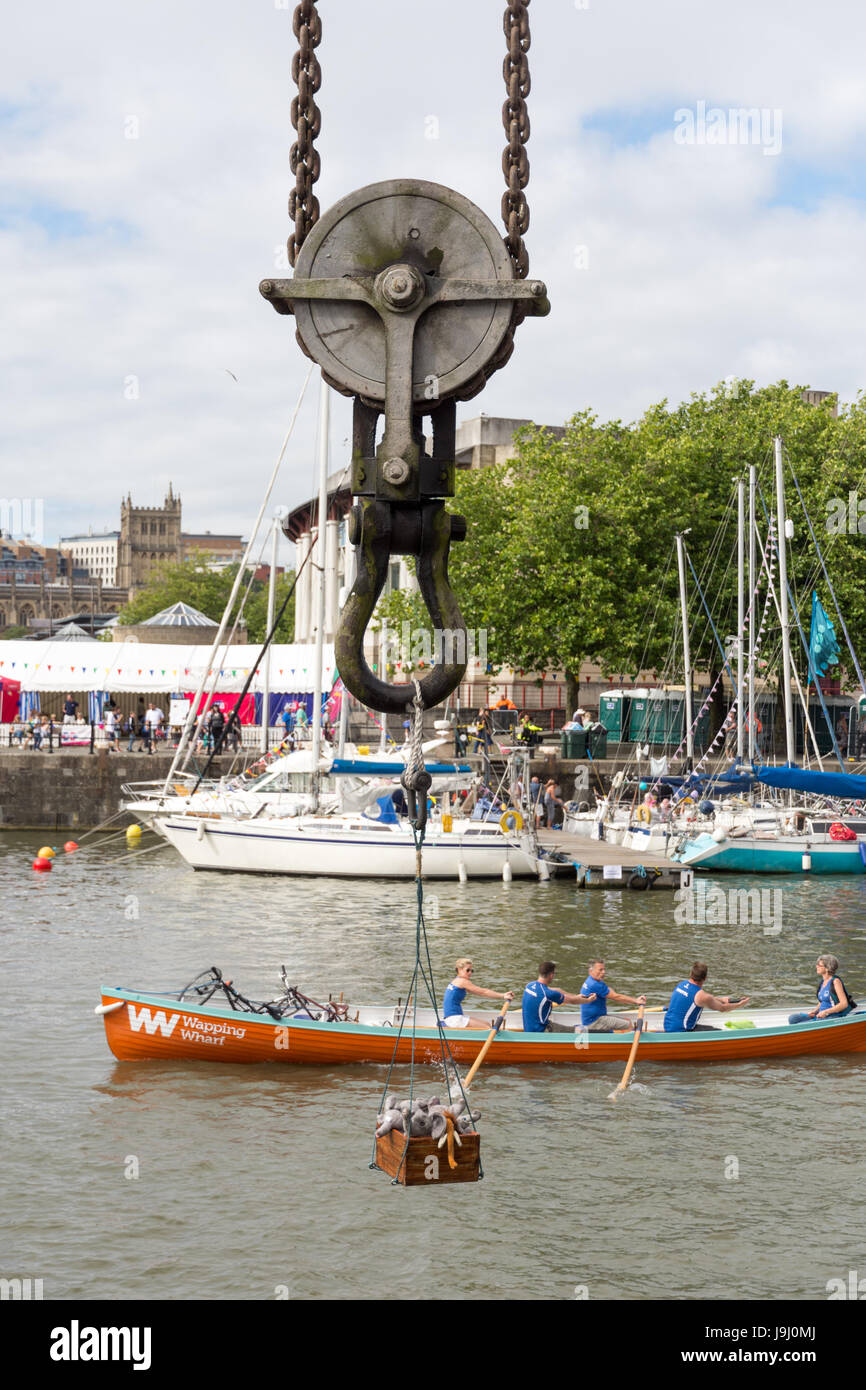 Bristol, England - July 17, 2016: A vintage dockside crane lifts a box of stuffed toys while a rowing team passes - Stock Image