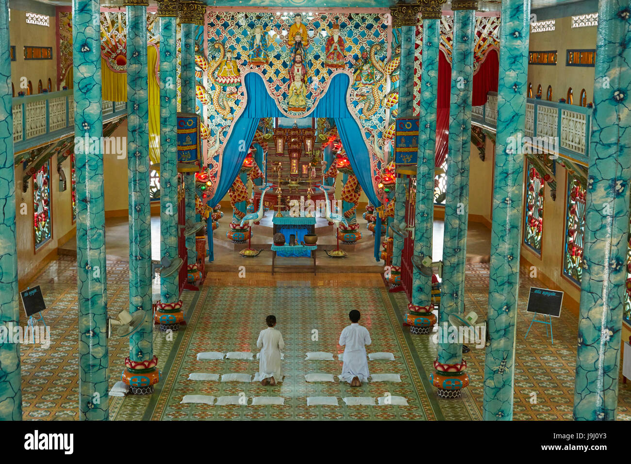 People praying inside Cao Dai Temple, Cai Lay town, Tien Giang province, Mekong Delta, Vietnam - Stock Image