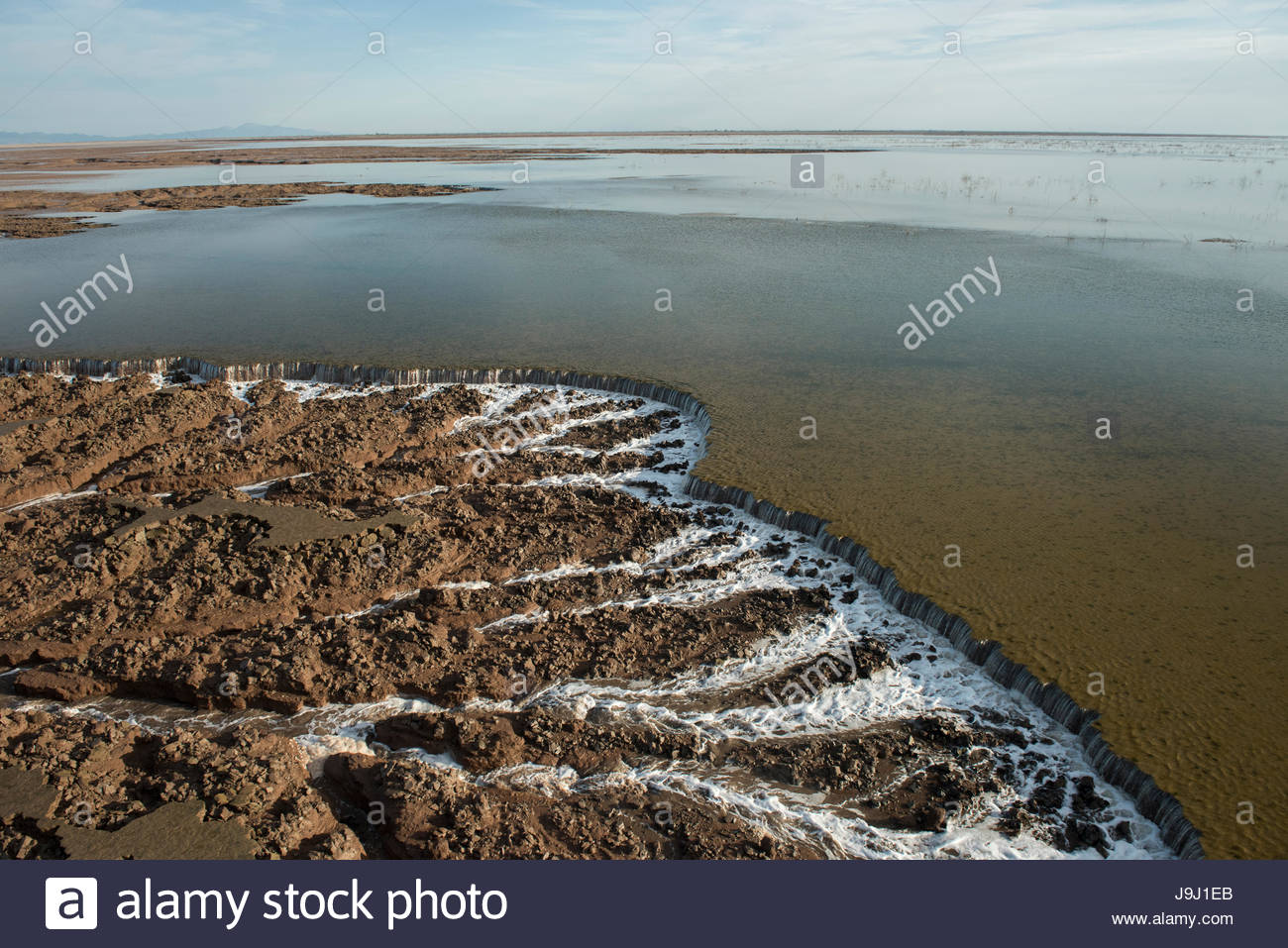 Ocean high tide waters downcutting tidal flat sand on the way back to the Sea of Cortez. - Stock Image