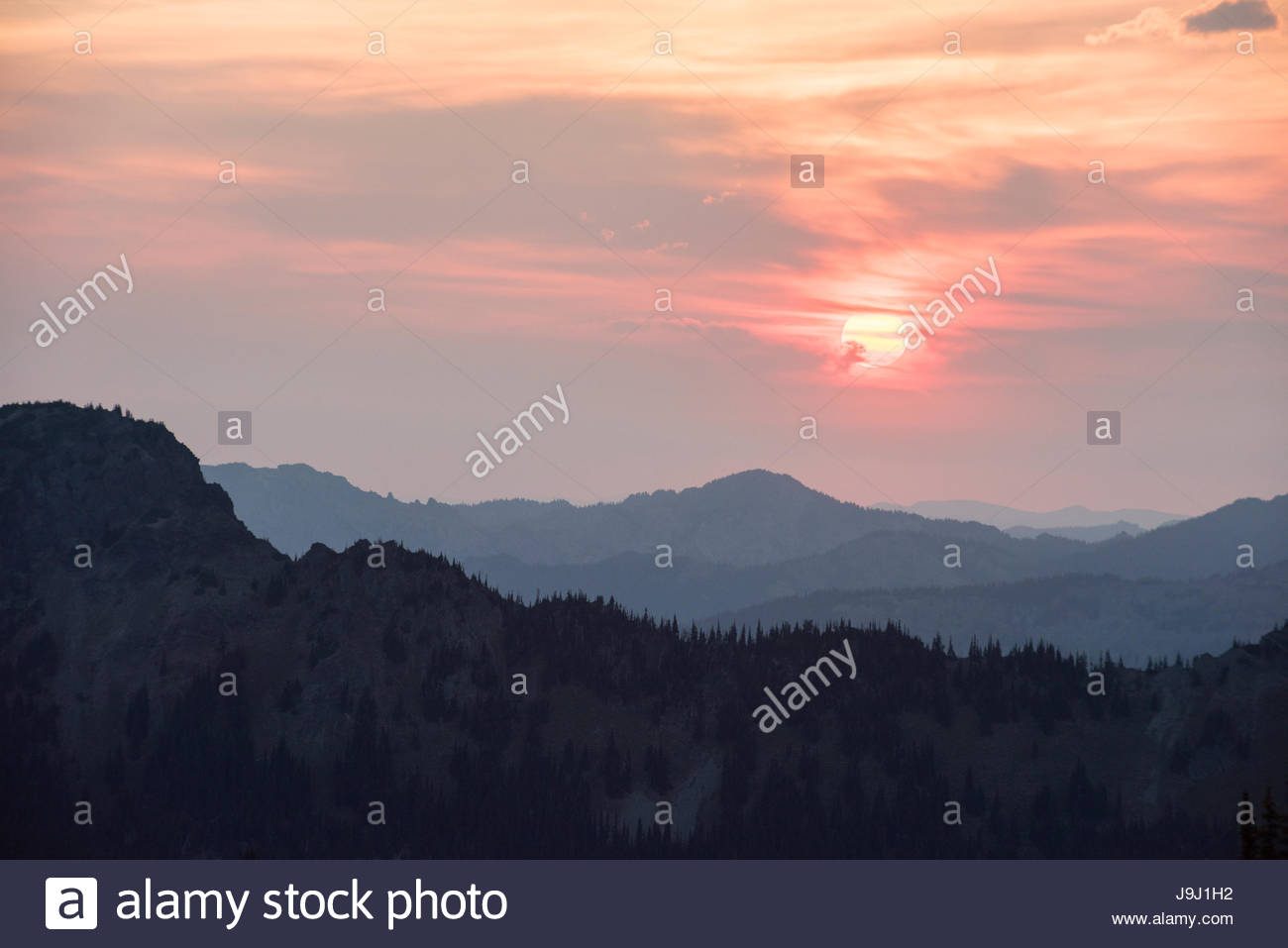 Nearby forest fires give the morning sun a reddish cast in Mount Rainier National Park. - Stock Image