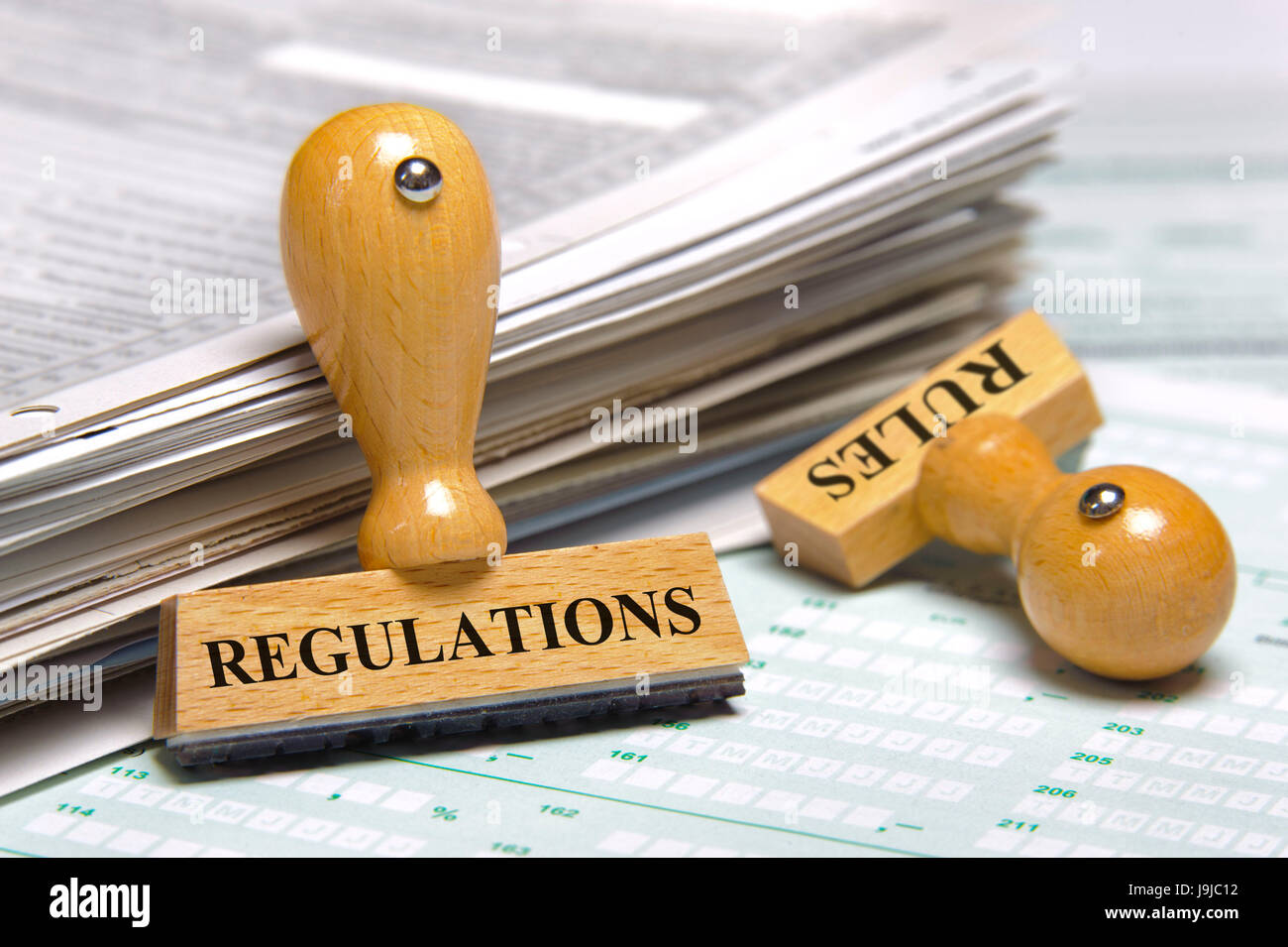 rubber stamps marked with regulations and rules - Stock Image