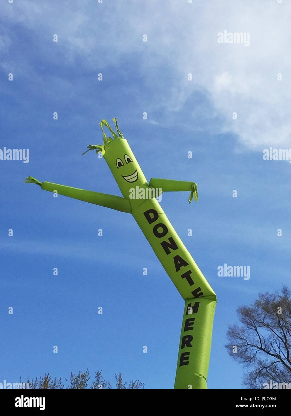 Donate Here inflatable cute cartoon character dancing against blue sky Stock Photo