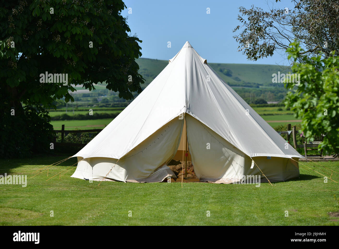 Canvas bell tent n the Sussex countryside with the South Downs in the background - Stock Image