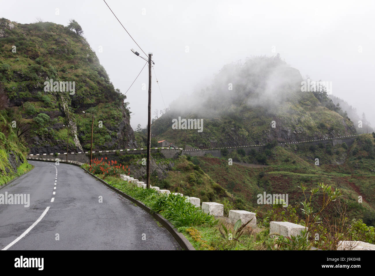 Low hanging cloud over a twisting mountain road in the centre of Madeira island - Stock Image