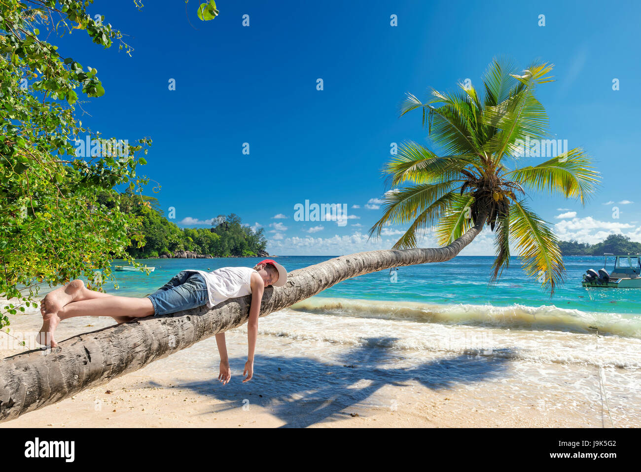 Cute boy resting lying on a palm tree at tropical island on vacationю - Stock Image
