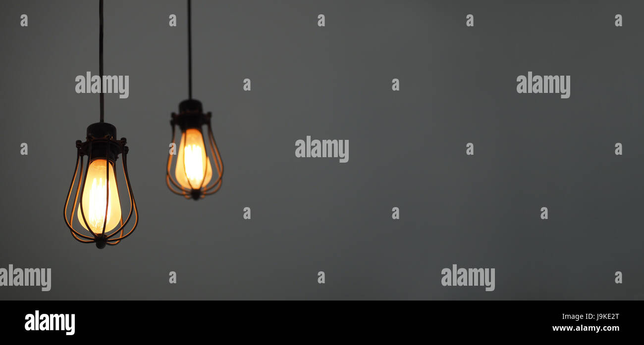 Yellow illuminated hanging light bulbs on plain background with free text space - Stock Image